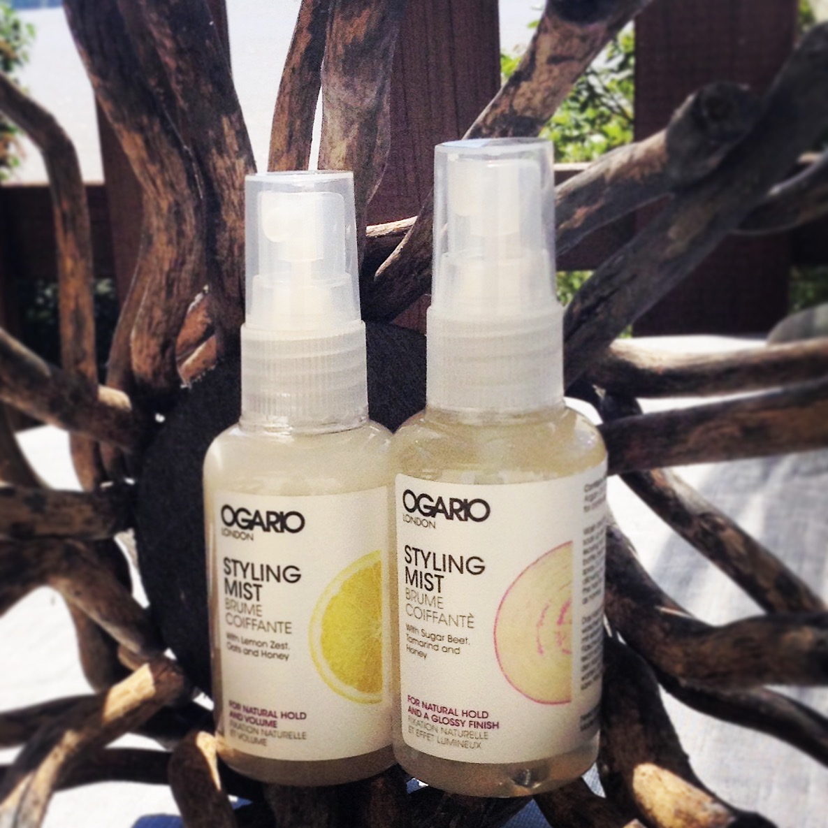 Ogario styling mist for volume and glossy finish set against wood backdrop