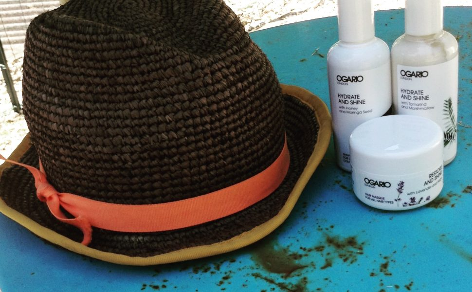 hat with orange band ogario london hydrate shampoo and conditioner and hair masque on a blue table